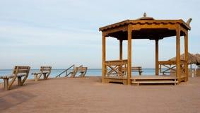 Alcova e bancos na praia A alcova de madeira grande e dois bancos na areia suportam Lugar vazio para encontrar-se perto do mar imagens de stock royalty free