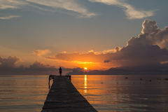 Alcudia boardwalk sunrise. Woman taking a photo of the sunrise on a boardwalk at Alcudia beach Royalty Free Stock Photos
