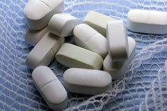 Alcune pillole bianche avvolte in garza su un fondo blu Fotografie Stock Libere da Diritti