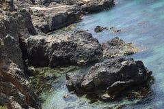 Alcune rocce nere che sono in chiaro mar Mediterraneo blu immagine stock