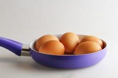 Uova sulla pentola, fondo bianco isolato Fotografia Stock