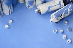 Alcuni bombolette spray ed ugelli blu utilizzati con i gocciolamenti della pittura si trova su una coperta del tessuto blu-chiaro immagine stock libera da diritti