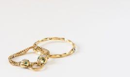 Alcuni braccialetti dell'oro su fondo bianco Modello di moda Jewelry Immagine Stock