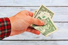 Alcuni dollari americani holded nel hamd dell'uomo vestito in SH a quadretti del lavoro Fotografia Stock