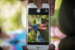 Alcuni giovani stanno prendendo le scarpe di un'immagine sul telefono in parco fotografia stock libera da diritti