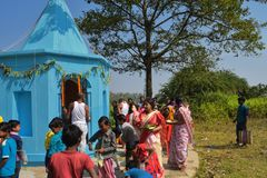 Alcuni uomini e donne che realizzano i rituali di puja camminando intorno al tempio e che distribuiscono i dolci ai bambini fotografie stock
