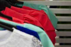 Alcuni vestiti utilizzati che appendono su uno scaffale in un mercato delle pulci Fondo del vestito Fuoco selettivo fotografia stock