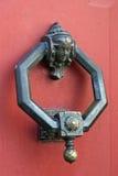 Aldaba de cobre en puerta roja Fotografía de archivo