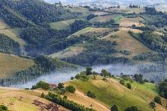 Aldea alpestre en montañas Fume, y neblina sobre las colinas en Cárpatos Foto de archivo