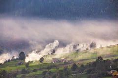 Aldea alpestre en montañas Humo, hoguera y neblina sobre las colinas fotos de archivo