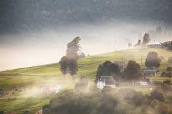 Aldea alpestre en montañas Humo, hoguera y neblina sobre las colinas imagen de archivo