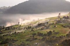 Aldea alpestre en montañas Humo, hoguera y neblina sobre las colinas fotografía de archivo libre de regalías