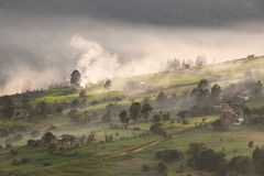 Aldea alpestre en montañas Humo, hoguera y neblina sobre las colinas fotos de archivo libres de regalías