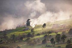 Aldea alpestre en montañas Humo, hoguera y neblina sobre las colinas foto de archivo