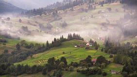 Aldea alpestre en montañas Humo y neblina sobre las colinas fotos de archivo libres de regalías
