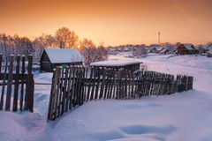 Aldea bajo nieve en el amanecer Foto de archivo libre de regalías