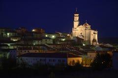 Aldea con la catedral por noche imagen de archivo