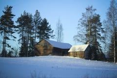 Aldea del invierno/edificios de madera bajo nieve Imagen de archivo libre de regalías