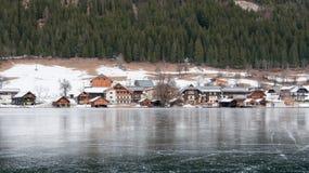 Aldea en el lago congelado de la montaña Imagen de archivo