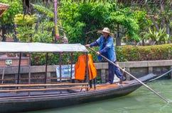 Aldeano indefinido pading el barco de madera tailandés tradicional en el mercado del flotador de Mayom del lat de Klong el 19 de  Foto de archivo libre de regalías