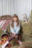 Aldeano y gato de la muchacha en pila del heno en granero Foto de archivo