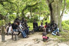 Aldeanos de Priumeri, Solomon Islands, sentándose debajo de árbol enorme en pueblo Imagenes de archivo
