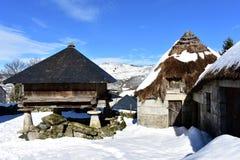 Aldeia da montanha nevado com as casas antigas do palloza feitas com pedra e palha e horreo galego do celeiro Piornedo, Lugo, Esp fotos de stock