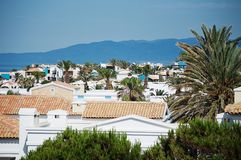 Greek village near the sea. Aldemar Cretan Village Resort. Beautiful, little, spectacular, greek buildings near the sea. Wide, clear sky, blue mountains and Royalty Free Stock Images