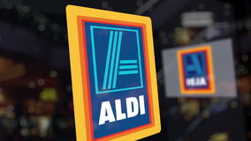 Aldi logo on the glass against blurred business center. Editorial 3D rendering Stock Images