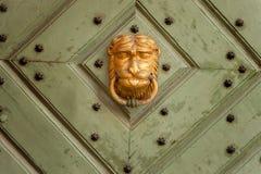 Aldrava de porta na forma de um leão dourado fotografia de stock royalty free