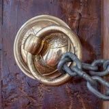 Aldrava de porta ornamentado de cobre antiga sobre uma porta de madeira envelhecida e uma corrente oxidada, Eyup Sultan Mosque, I imagem de stock