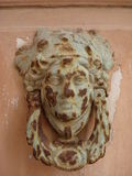Aldrava de porta oxidada na forma da cara de uma mulher romana clássica Imagem de Stock