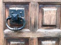 Aldrava de porta preta do metal, botão de porta com um anel para bater no fundo de uma porta velha marrom de madeira do vintage imagem de stock royalty free