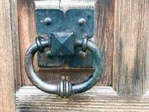 Aldrava de porta preta do metal, botão de porta com um anel para bater no fundo de uma porta velha marrom de madeira do vintage fotos de stock royalty free