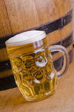 Ale. Full glass of Ale with wooden barrel, blond beer with foam Stock Photo
