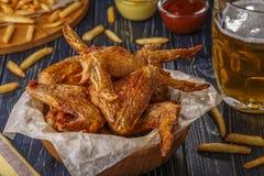 Ale di pollo fritte con le patate fritte e la birra fotografia stock libera da diritti