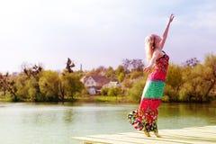 Alegría del baile: mujer delgada joven rubia hermosa que disfruta de estirar en vestido ligero largo en el lago del agua en verde Fotografía de archivo