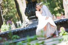 Alegría del novio y de la novia contra la fuente del contexto fotografía de archivo libre de regalías