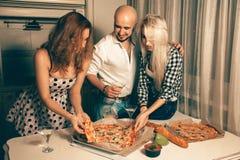 Alegría feliz de los estudiantes un partido del hogar con la pizza y el alcohol imagen de archivo libre de regalías