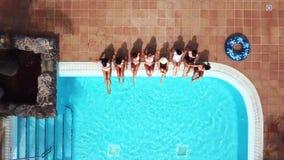 Alegría y amistad con un grupo de mujeres que se divierten jugando con el agua en la piscina - vacaciones de verano almacen de video