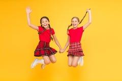 Alegr?a verdadera niñas felices en falda a cuadros Mirada de la belleza niños felices en fondo amarillo Felicidad de la ni?ez fotos de archivo