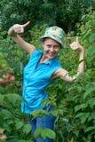 Alegre, chica joven en el jardín, colocándose con las frambuesas adentro Imagen de archivo libre de regalías
