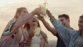 Alegre e apreciando a vida da empresa de meninas e de meninos dos vidros do tim-tim dos povos cocktail urbano do verão video estoque