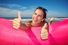Alegre y la risa suavemente de la mujer está mintiendo en boa inflable rosada imagen de archivo libre de regalías