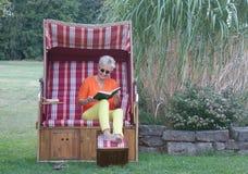Alegremente com um riso em sua cara, a mulher loura lê dentro o livro cômico foto de stock