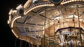 Alegres iluminados vão círculo no parque Carrossel brilhantemente iluminado que gerencie no parque de diversões maravilhoso na no vídeos de arquivo