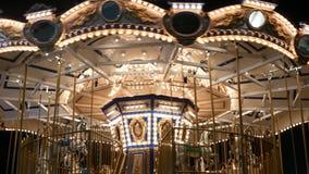 Alegres iluminados v?o c?rculo no parque Carrossel brilhantemente iluminado que gerencie no parque de divers?es maravilhoso na no vídeos de arquivo