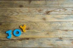 Alegria de madeira colorida da palavra em floor1 de madeira Fotografia de Stock Royalty Free