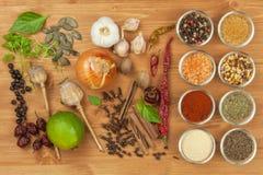 A alegria do cozimento, preparação das especiarias Vários tipos das especiarias em uma placa de madeira Preparação de alimento Fotos de Stock