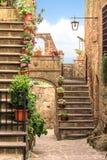 Aleia bonita com flores e escadas em uma vila pequena Imagem de Stock